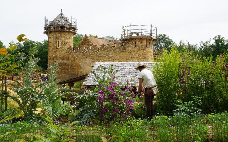 2—Guedelon–Le-jardinier-avec-la-courtine-oeust-en-arriere-plan