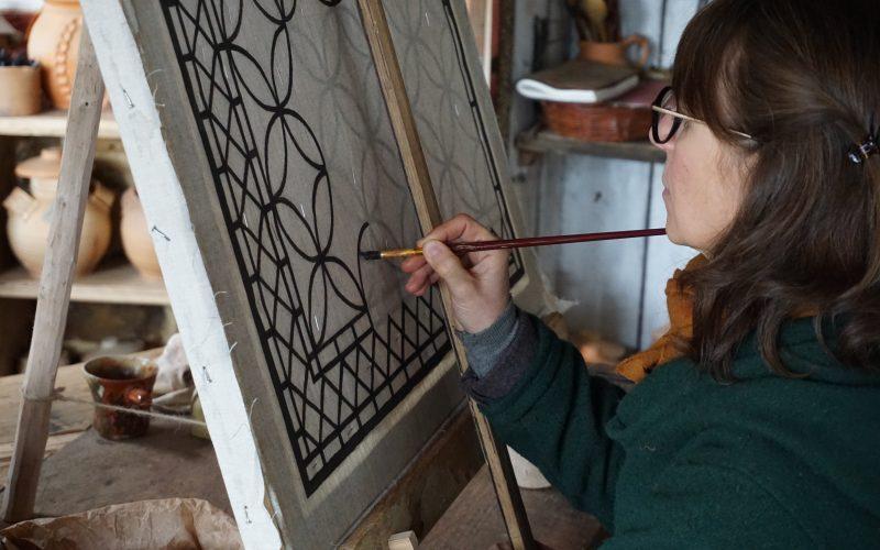 La peintre décore une fenêtre en toile cirée ©Guédelon