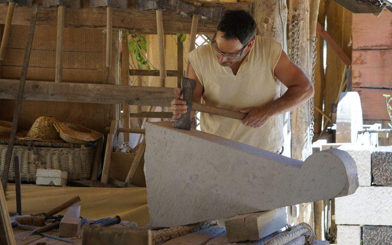 Un tailleur de pierre taille la marche d'un escalier en vis